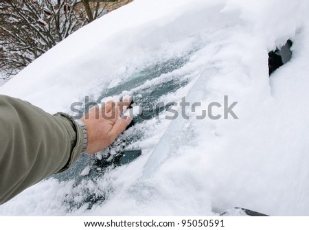 Removing snow from car with a hand