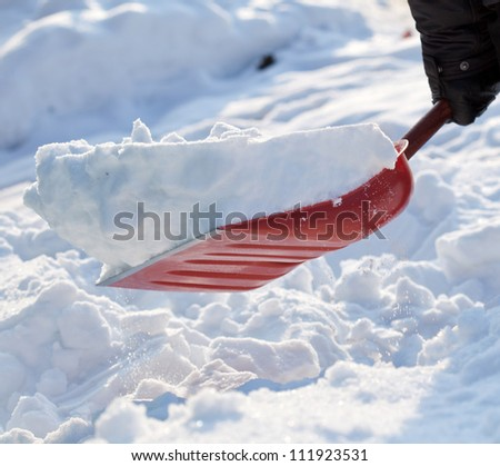 Removing snow with a shovel after snowfall - stock photo
