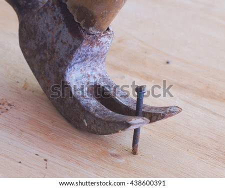 removing the nail with a hammer - stock photo