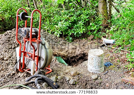 Removing tree roots from groundwater drainage pipe in a back yard - stock photo