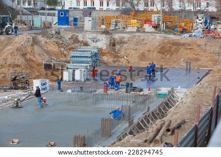 Renaissance construction workers reinforce fitting. The concrete foundation of the hotel building.Polishing concrete special tools.  Belarus,Minsk,November,1,2014 - stock photo