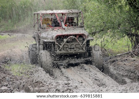 Rence, Slovenia - May 31, 2015: Offroad car in red 4wd vehicle is driving through mud and water in full speed.