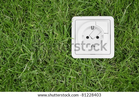 Renewable energy concept - electric outlet on grass - stock photo
