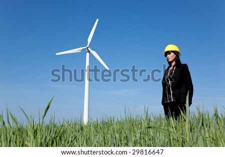 Renewable energy constructor standing on green field behind blue sky with windmill - stock photo