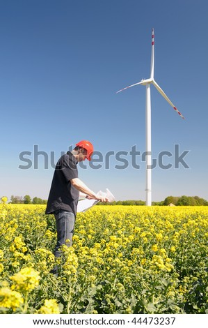 Renewable energy constructor standing on yellow field of rapeseed, behind blue sky with windmill. - stock photo