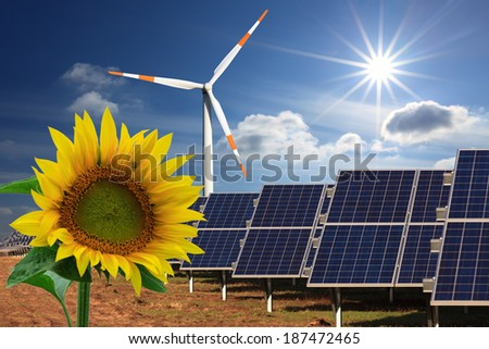 renewable energy: windmill, solar panel and sunflower - stock photo