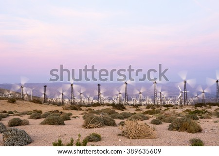 Renewable energy windmills line the mountaintops of Palm Springs during sunset - stock photo