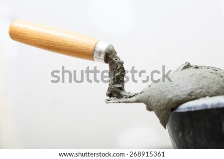 Renovation at home dirty trowel and bucket with mortar on construction building site - stock photo