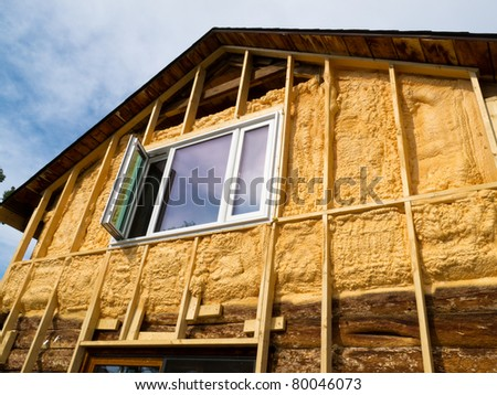 Renovation of old house: wall is sprayed with liquid insulating foam before the siding goes on. - stock photo