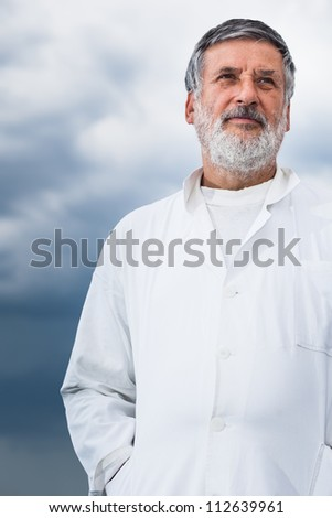 Renowned scientist/doctor standing on the roof of the research center/hospital looking confident (color toned image) - stock photo