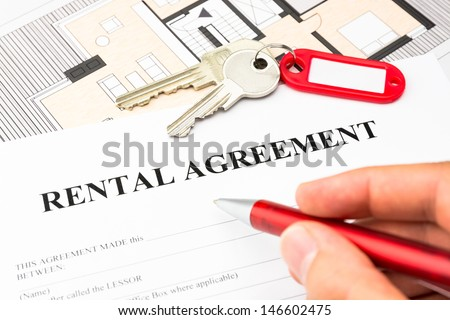 rental agreement contract with red pen and male hand and keys - stock photo