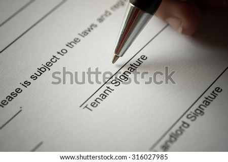 Rental agreement form with signing hand and pen. - stock photo