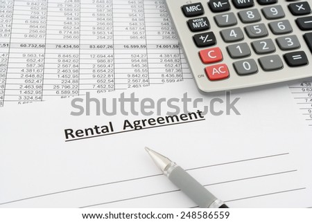 rental agreement with numbers, calculator and pen - stock photo