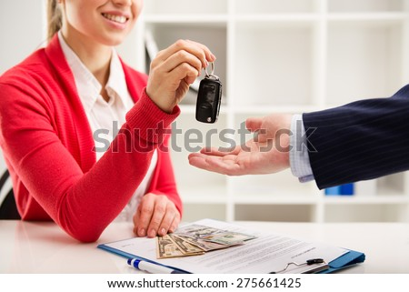 Rental contract. Transport purchase. Woman automotive dealer offering car key to buyer. Shallow depth of field. - stock photo