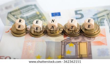 Rente cube on money - Rente means pension - stock photo