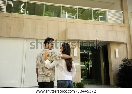 Renting or buying an apartment: Couple standing in front of their new flat - stock photo