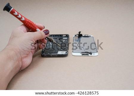 repair a smartphone using a screwdriver - stock photo