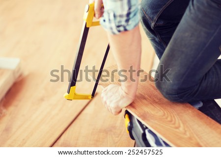 repair, building and home concept - close up of male hands cutting parquet floor board with saw - stock photo