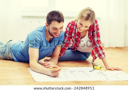 repair, building, renovation and home concept - smiling couple looking at blueprint at home - stock photo