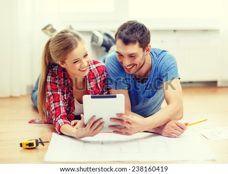 repair, building, renovation and home concept - smiling couple looking at tablet pc at home - stock photo