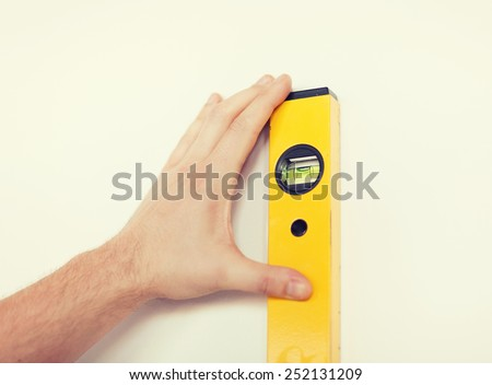 repair, building, technology and home concept - close up of male with spirit level mesuring wall - stock photo