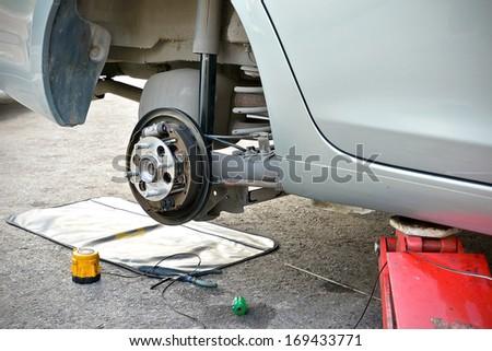 Repair car brake in garage - stock photo
