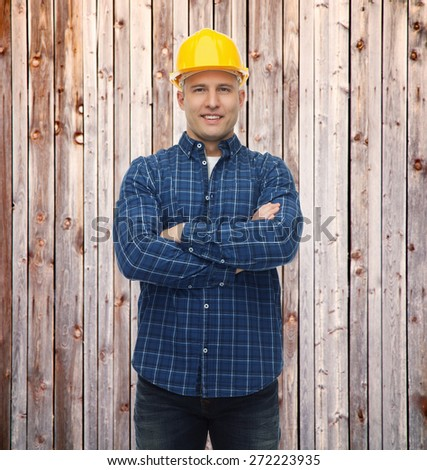 repair, construction, building, people and maintenance concept - smiling male builder or manual worker in helmet over wooden fence background - stock photo