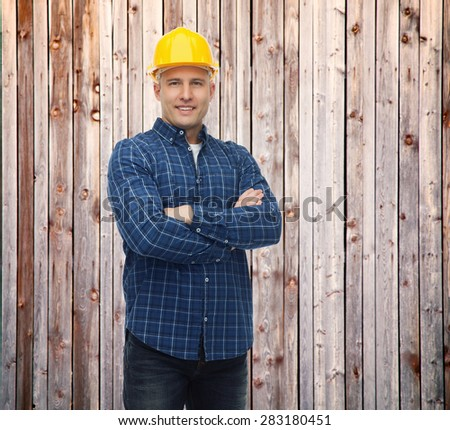 repair, construction, building, people and maintenance concept - smiling male builder or manual worker in helmet over blue background over wooden fence background - stock photo