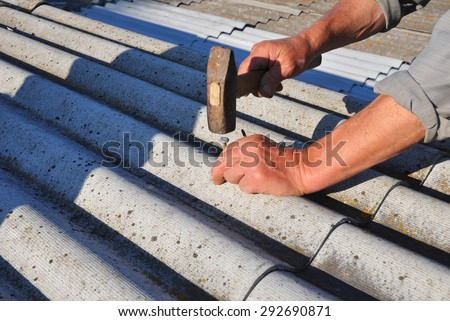 Repair dangerous asbestos old roof tiles. Worker installs asbestos roof shingles - closeup on hands. Asbestos has not been used in domestic building materials since the 1980. - stock photo
