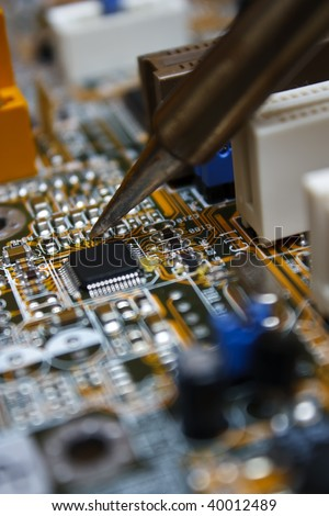 Repair electronic circuit board with soldering iron - stock photo
