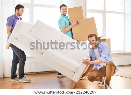 repair, furniture, decorating and home concept - smiling friends with sofa and cardboard boxes - stock photo