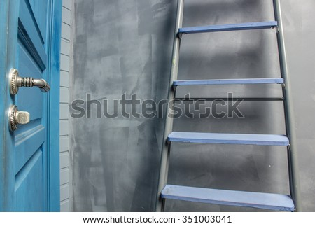 repair in an apartment by using a stepladder which costs around blue door leaning on the wall