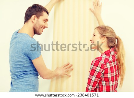 repair, interior design, building, renovation and home concept - smiling couple choosing wallpaper for new home - stock photo