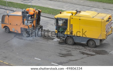 Repair machines fixing a pothole in a road caused by frost - stock photo