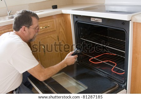 Repair man testing the operation of stove & oven - stock photo