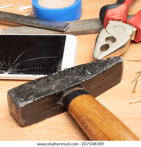 Repair mobile phone composition of a smartphone with a broken screen next to the multiple tools over a wooden surface