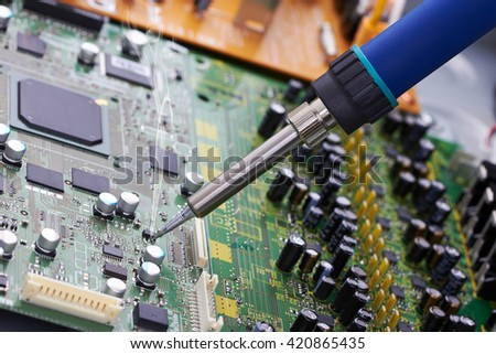 Repair of electronic devices, soldering parts - stock photo