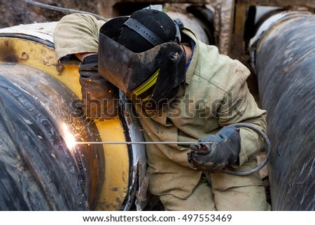 Repair of heating duct. The workers, welders made by electric welding and gas welding on large iron pipes at a depth of excavated trench.