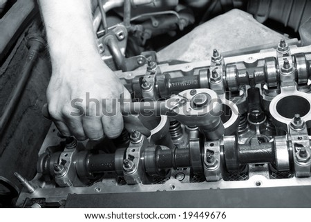 Repair of the engine. A hand with the tool. Automobile service.monochrome