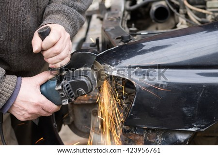 Repair service worker fix damaged car after crash on the road. Working with angle grinder to fix metal body. - stock photo