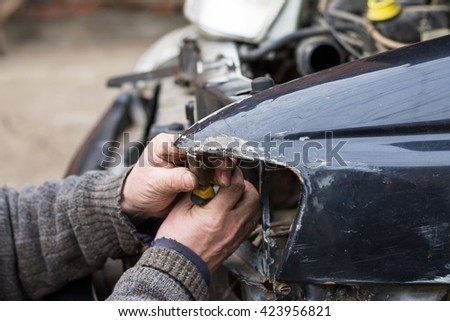 Repair service worker fix damaged car after crash on the road. Working with pliers to align metal body. - stock photo
