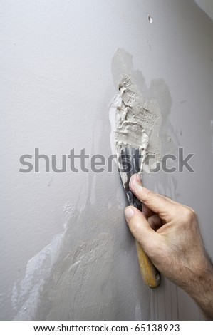repair the damage to plaster a wall with gray paint - stock photo