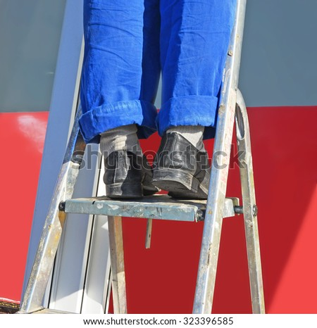 Repair. The worker's feet in a uniform on a step-ladder near a wall. Too long pants are rolled up. Soles of boots worn out. Spots of paint and a lime on a step-ladder. - stock photo