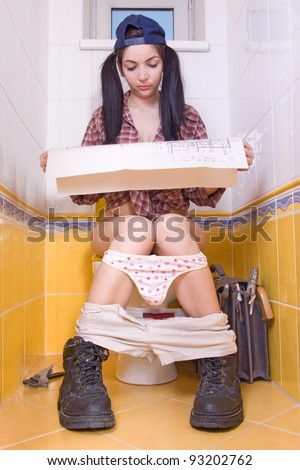 Repair-woman sit on a toilet with the construction plans of the building. Female craftsman study house plans on the toilet.