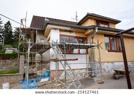 repaired rural house, fixed facade, insulation and painted to green  color witg swimming pool - stock photo