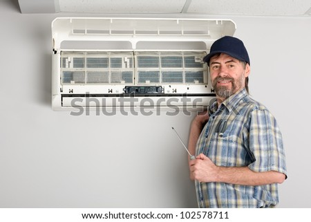 Repairer conducts adjustment of the indoor unit air conditioner - stock photo