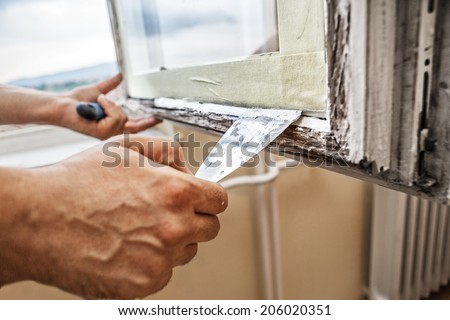 Repairing a window frame -Man using scraper and putty for renovation old windows - stock photo