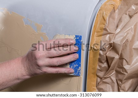 repairing an old car with surfacer and spatula - stock photo