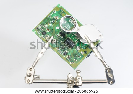 Repairing microprocessor with magnifying glass and robot hands - stock photo