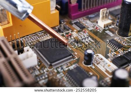 Repairing of computer motherboard, macro view - stock photo